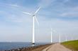 Wind turbines standing along the dyke in the Dutch sea