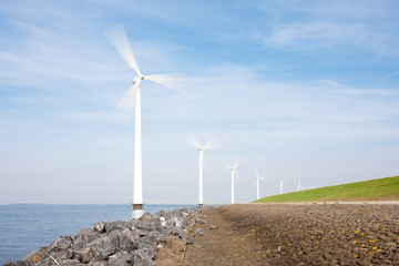 Spinning windturbines standing in the sea photographed with long