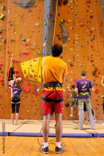 Homme assurant un grimpeur au mur d'escalade