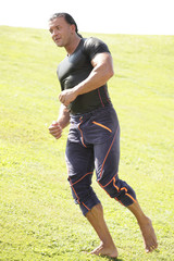 Athletic man running in the field