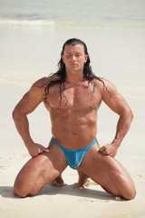 Bodybuilder meditating on the sand with eyes closed
