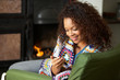 Young woman sitting by fire with phone