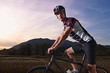 portrait of man training on mountain bike at sunset
