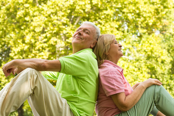 Happy senior couple sitting on grass