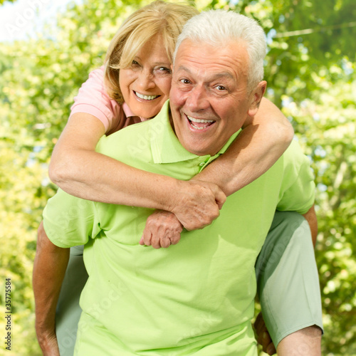 happy senior man giving piggyback senior woman