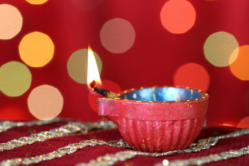 Diwali Diya with blurred festive lights in the background