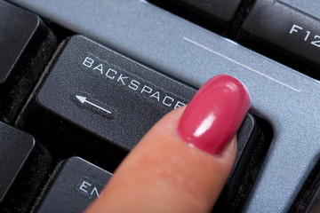 "woman finger pushes ""Backspace"" button"