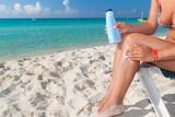 Woman applying sun blocker on the beach poster