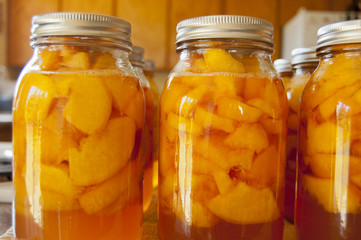 Glass jars of home canned peaches
