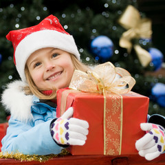 Merry Christmas -  girl in sledge with Christmas gift