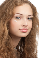 Woman with drops of moisturizer cream on her face