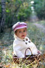 Lovely little girl sitting in the forest