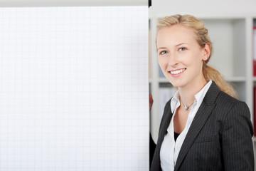 lächelnde blonde geschäftsfrau steht am flipchart