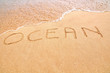 Ocean text written on the beach sand