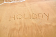 Holiday text written on the beach sand
