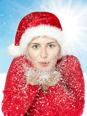 Nice woman with Santa Claus hat blowing snow in winter