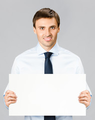 Business man showing blank signboard, over gray