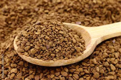 Ground coffee with wooden spoon close-up