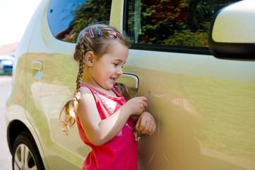 Kind  verkratzt ein Auto