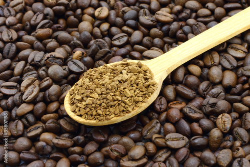 Ground coffee in wooden spoon on a coffee beans background