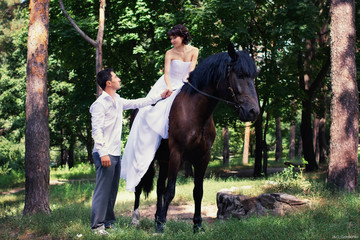Bride and groom posing in the garden with a horse