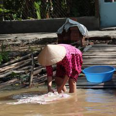 donna che lava i panni nel mekong