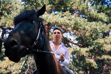 groom posing on a horse in the forest