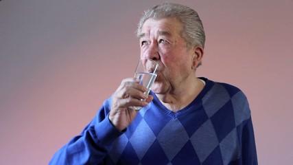 Senior trinkt durstig ein Glas Wasser