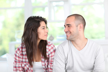 Young couple at home sitting in couch