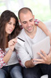 Young couple doing online shopping using electronic tablet