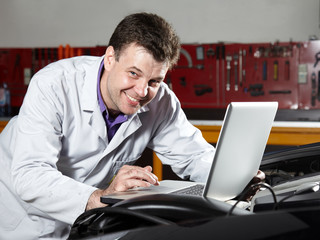 Motor mechanic is tuning the engine of a car
