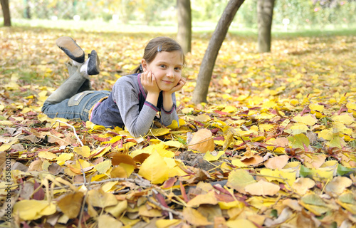 girl lying on fall leaves outdoors