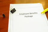 Employee benefits package on a desk with misc office supplies poster