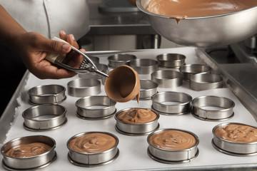 Cuisinier garnissant des moules de mousse au chocolat