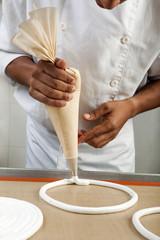 Cuisinier formant des cercles de meringue avec une poche à douille