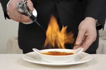 Caraméliser une crème brûlée au chalumeau