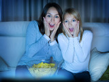 Mother with Daughter watching film on TV
