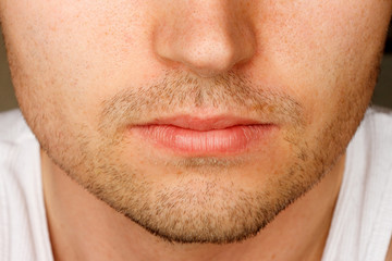 Close up of man's face sporting a 5 o'clock shadow