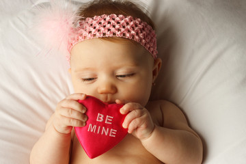 Baby holding a heart that says Be Mine