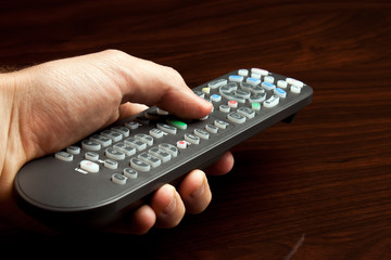 Hand pointing television remote against wooden surface