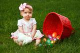 Baby girl frowning beside a spilled Easter egg basket