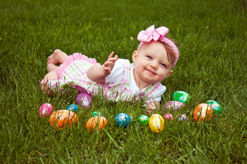 Beautiful baby laying in grass with Easter eggs