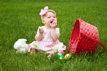 Baby Smiling while holding an Easter egg beside basket