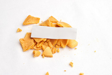 Top view of smashed fortune cookie with blank white slip