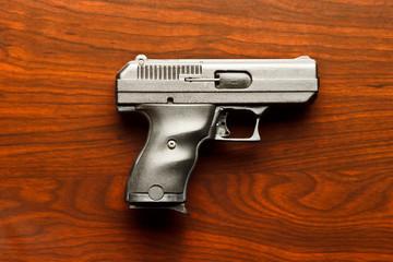 Top view of 9 mm handgun against wooden surface