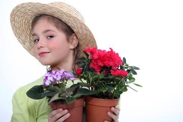 little girl  holding two flowerpots
