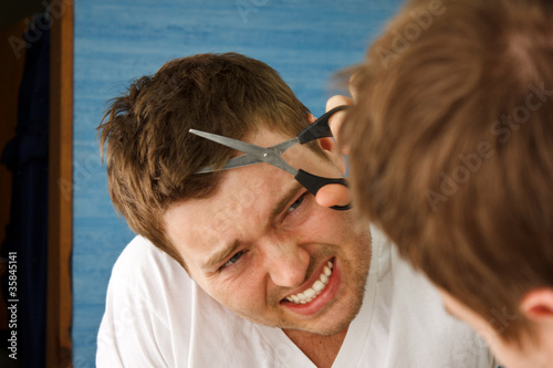 Young man preparing in mirror to cut hair himself