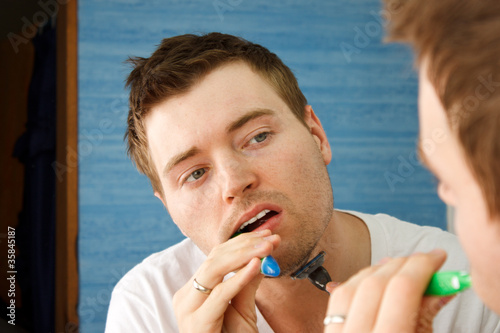 Man multitasking by brushing teeth and shaving