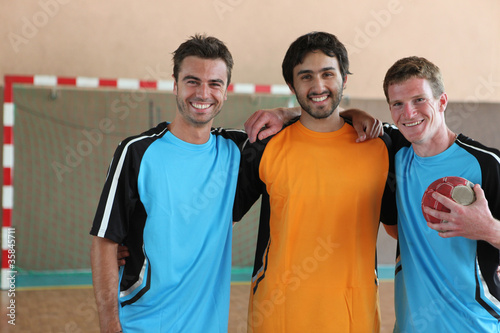 Three grinning footballers in front of goal