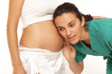 Frau legt Kopf an den Bauch einer Schwangeren